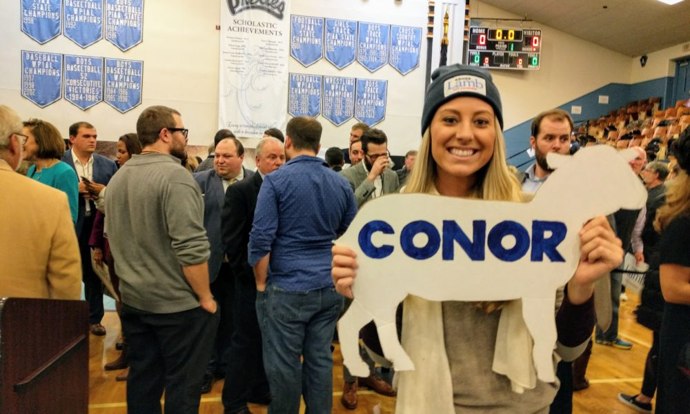 """Young female Conor Lamb supporter holding a lamb cutout with """"Conor"""" inscribed on it at the nominating convention."""